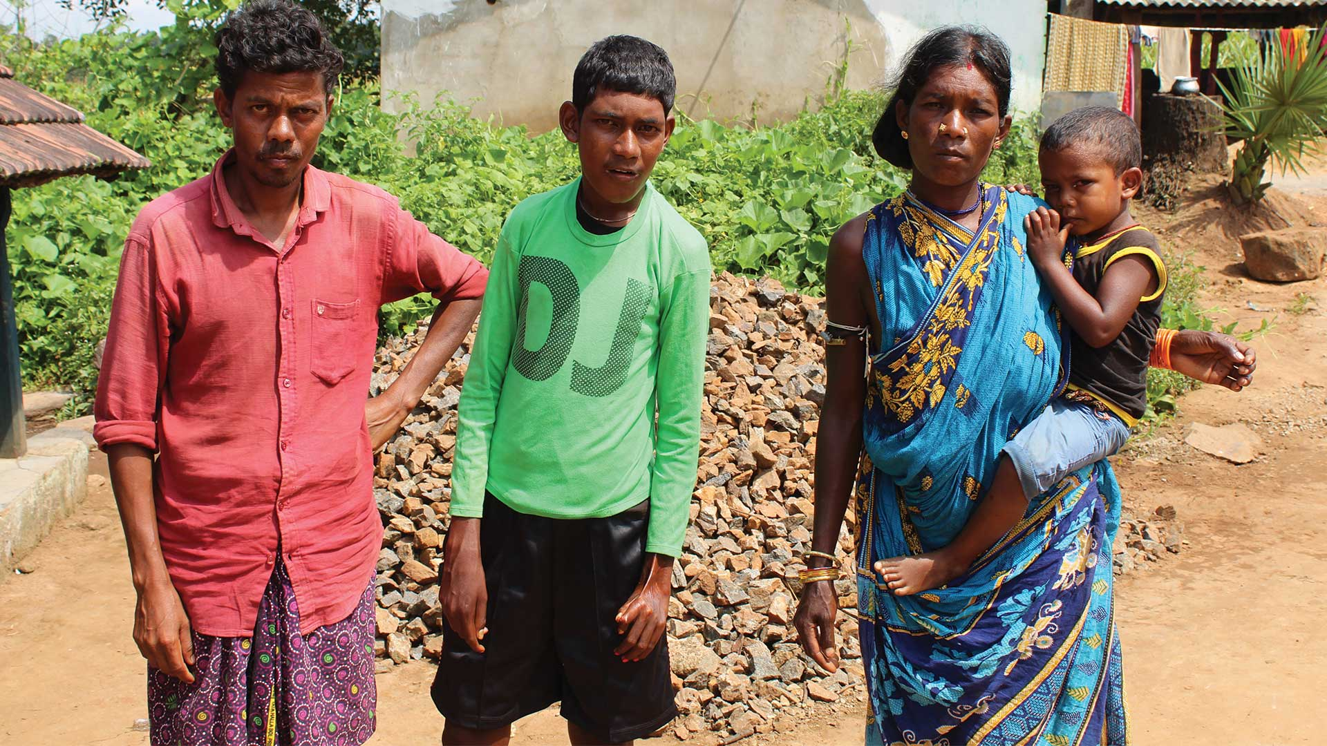 Mother, father, teenage son and baby stood outside in village in India