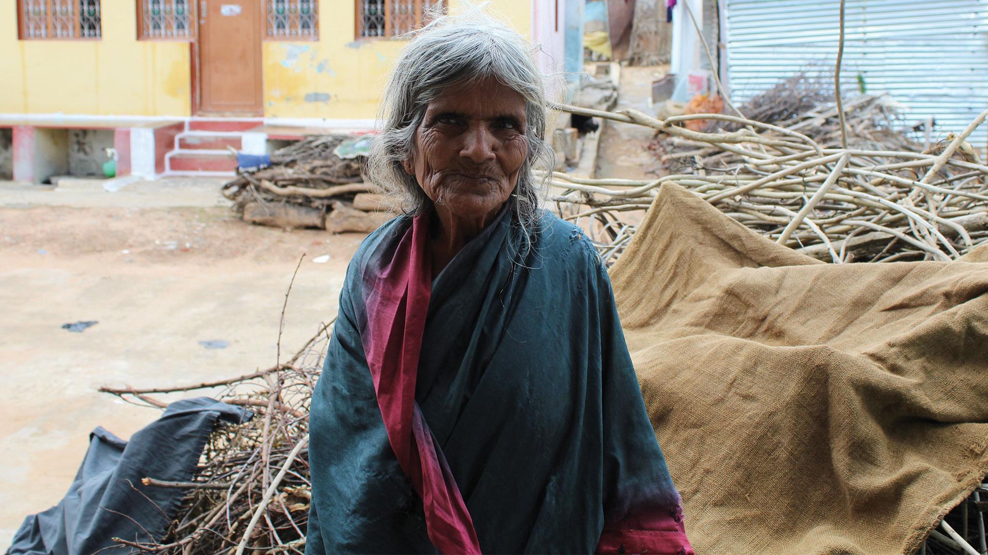 Elderly carer stood outside in India