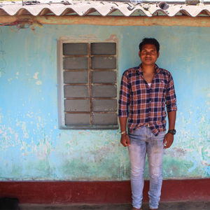 Male carer stood outside his house in India