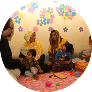 Two female carers and their two children and CDD staff member at Community Caring Centre