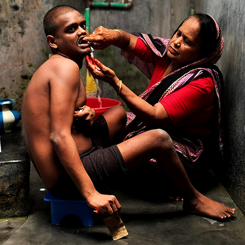 Carer brushing the teeth of her adult son