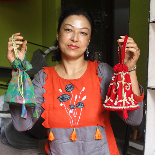 Carer holding two bags that she made