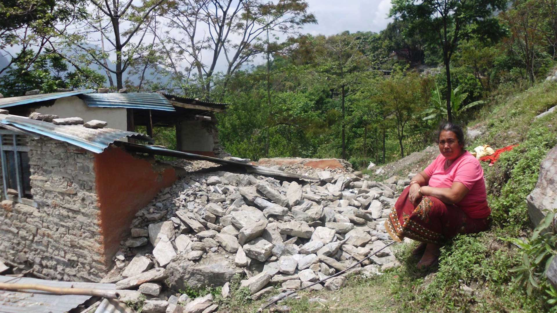 Carer next to earthquake damaged home in Nepal