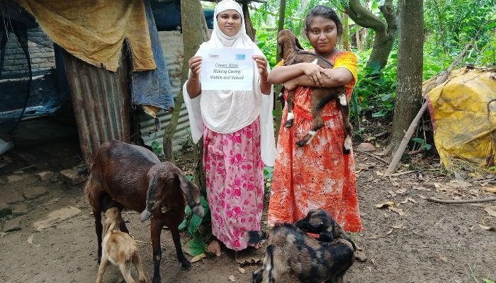 A woman and a girl standing outside with some goats