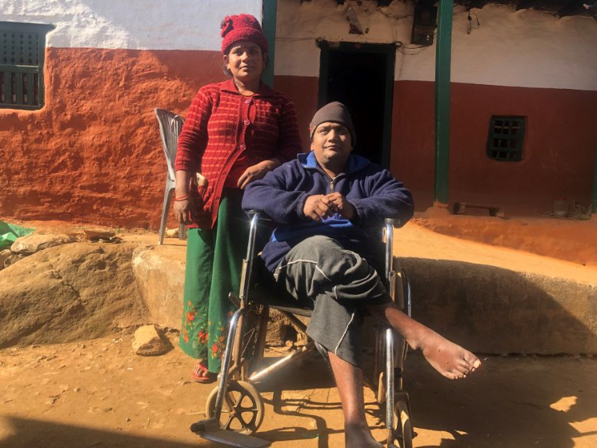 Woman standing next to a man in a wheelchair, outside.