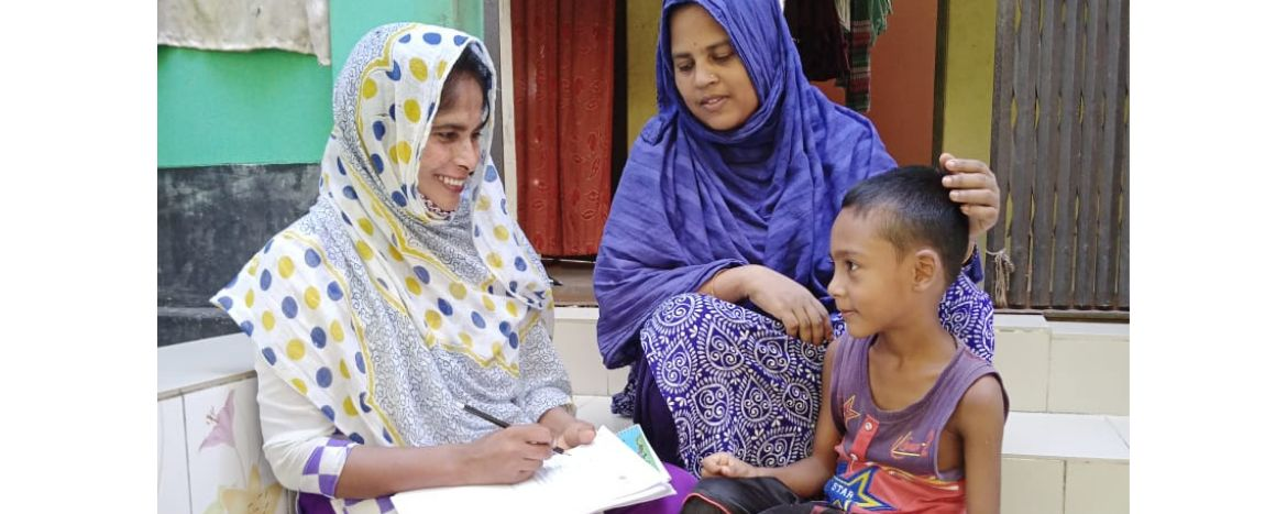 Two women and a child sitting together, one woman writing answers to a survey