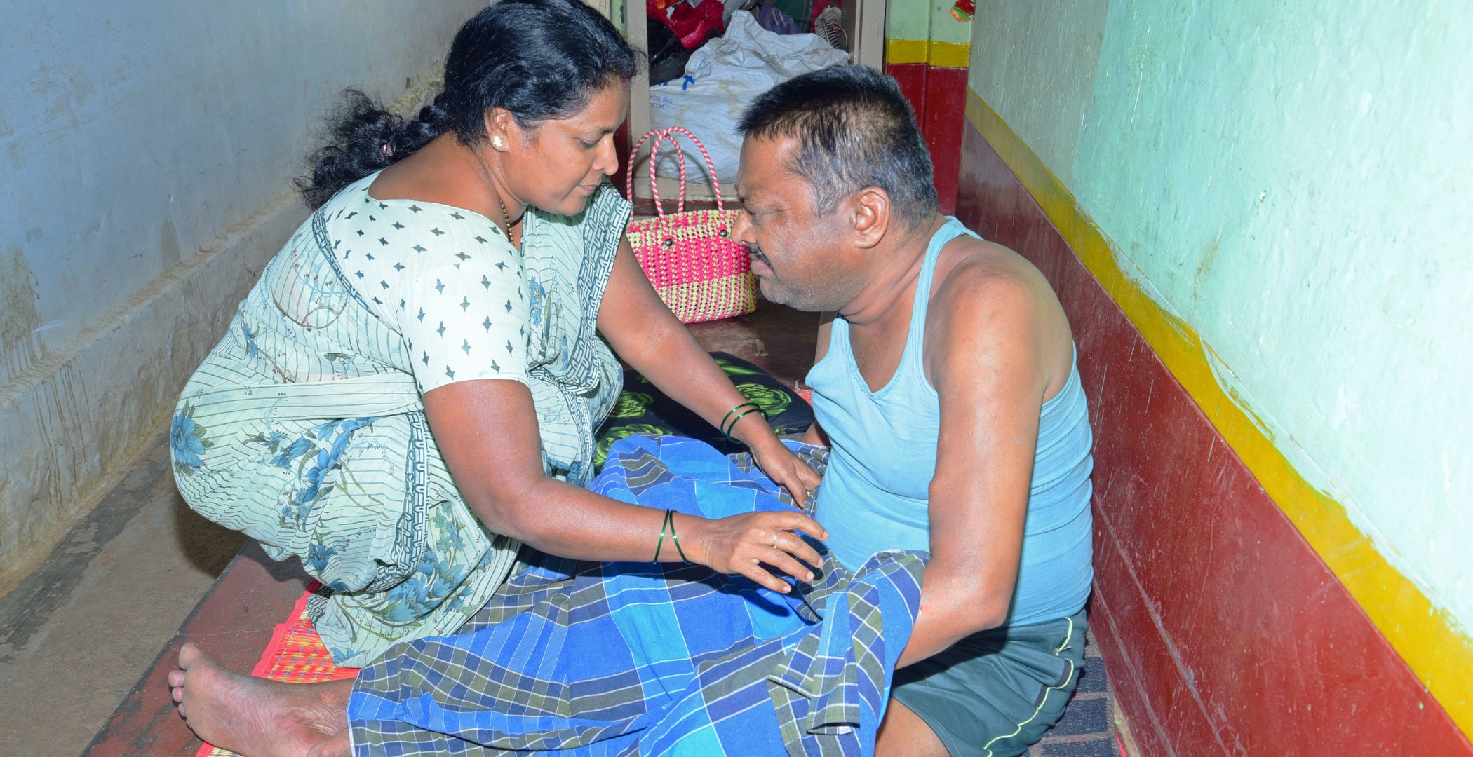 Woman and man sitting on the floor inside: woman caring for her husband